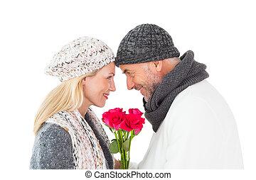 Pareja sonriente en invierno posando con rosas