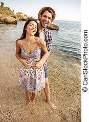 Pareja sonriente enamorada parada en la playa y abrazando