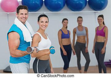 Pareja sosteniendo pesas con clase de fitness en el fondo