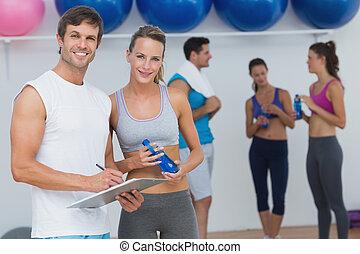 Pareja sosteniendo portapapeles con clase de fitness en el fondo