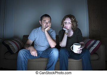 Pareja viendo la televisión aburrida