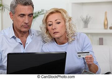 Parejas de mediana edad comprando en línea.