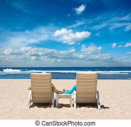Parejas en sillas de playa sosteniendo manos cerca del océano