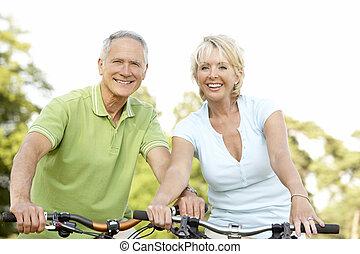 Parejas maduras montando bicicletas