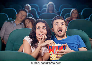 Parejas viendo películas de terror. Gente aterrorizada viendo películas en el cine