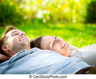 Park. Una pareja joven tirada en la hierba al aire libre