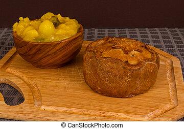 Pastel de juego servido con tazón de piccalilli