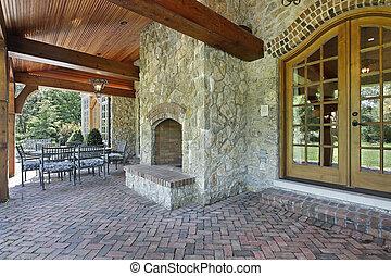 patio de ladrillos con chimenea de piedra