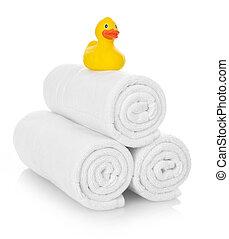 Pato de goma en toallas blancas