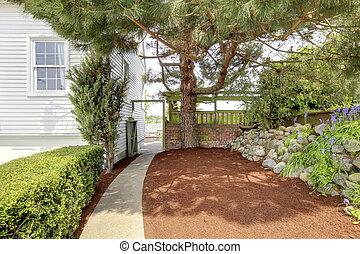 Patrón lateral con camino y gran árbol cerca de la casa blanca.