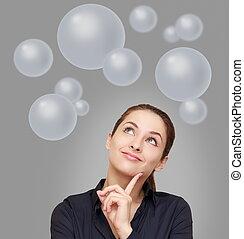 Pensando en una mujer de negocios mirando muchas burbujas sobre fondo gris