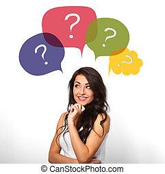 Pensando en una mujer sonriente con muchas preguntas coloridas en burbujas sobre la cabeza sobre fondo blanco