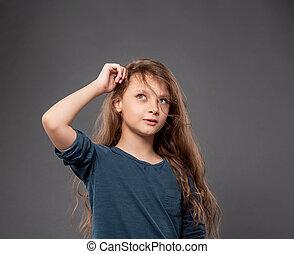 Pensando en una niña sonriente rascándose la cabeza y mirando hacia arriba en el fondo oscuro del estudio gris con espacio de copia vacío.