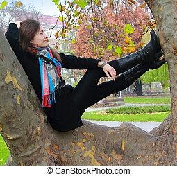 Pensar que una mujer se relaja en un árbol y mira con sonrisa en el color de otoño