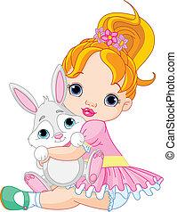 Pequeña chica abrazando al conejito de juguete