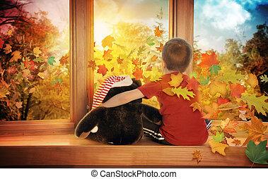 Pequeña niña mirando hojas de otoño en la ventana