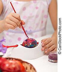 Pequeña niña pintando huevos de Pascua
