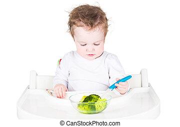 Pequeño bebé comiendo brócoli, aislado en blanco