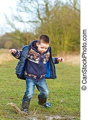 Pequeño niño salpicando en un charco en el campo