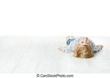 Pequeño niño tirado en el suelo
