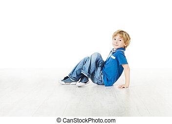 Pequeño sonriente sentado en el piso y mirando la cámara