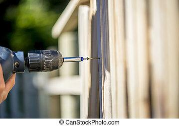 Persona construyendo una cerca de madera con un taladro y tornillo