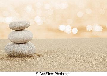 Piedras balanceadas en arena en blanco
