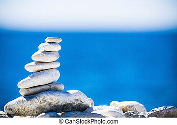 Piedras balanceadas, piedras apiladas sobre el mar azul en Croacia.