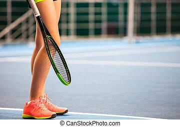 Piernas de jovencita en una pista de tenis cerrada con raqueta