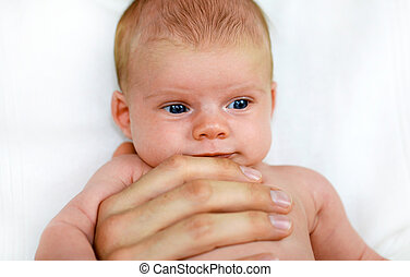 Pies de bebé y manos de papá adulto.