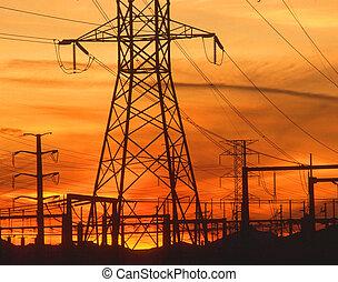 Pilones de electricidad al atardecer naranja
