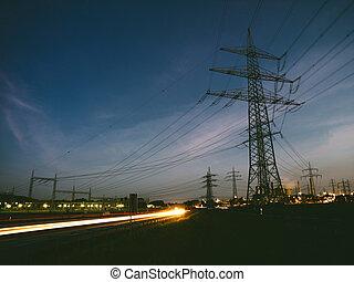 Pilones eléctricos al atardecer transportando energía limpia