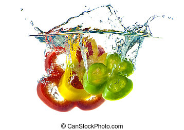 Pimienta roja, amarilla y verde, salpicada en agua azul clara, aislada con fondo blanco.