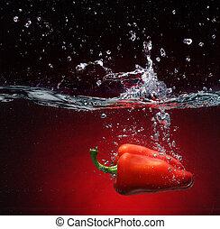 Pimienta roja cayendo al agua