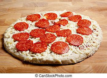 Pizza de pepperoni congelada en una tabla de cortar