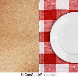 Placa blanca en la mesa con mantel rojo