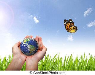 Planeta Tierra y mariposa en mano femenina en el cielo azul