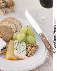 Plata de queso y galletas con un vaso de oporto
