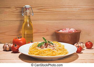Plato de sabroso espagueti con salsa de tomate y carne en la mesa de madera.