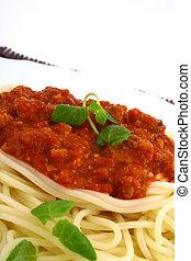 Plato recién cocinado de espagueti con hierbas verdes frescas.