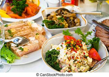 Platos con bocadillos fríos en la mesa, cubiertos para la cena, servilleta blanca, enfoque selectivo.