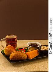 Ploughmans almuerza con queso leicester rojo y media pinta de cerveza inglesa.