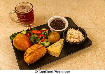 Ploughmans almuerza con queso stilton y media pinta de cerveza inglesa.