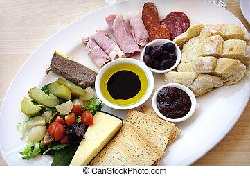 Ploughmans Almuerzo plato de antipasto incluyendo, pan crujiente, queso, carne fría, jamón, aceitunas, aceite de oliva y vinagre balsámico, galletas, paté y ensalada.
