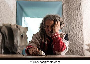 Pobre hombre de pelo gris mirando una bombilla de ajo fresco