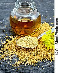 Polvo de mostaza en cuchara con aceite y flor a bordo