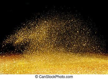 Polvo dorado esparcido por el fondo oscuro
