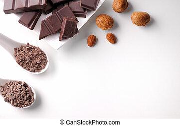 Porciones y chips de chocolate en contenedor con almendras aisladas
