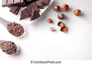 Porciones y chips de chocolate en contenedor con avellanas aisladas