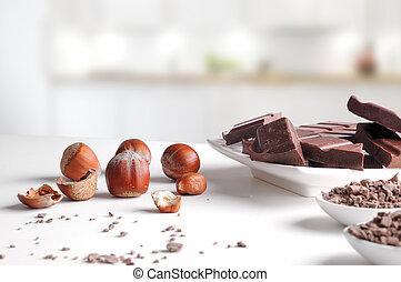 Porciones y chips de chocolate en contenedores con avellanas en la cocina